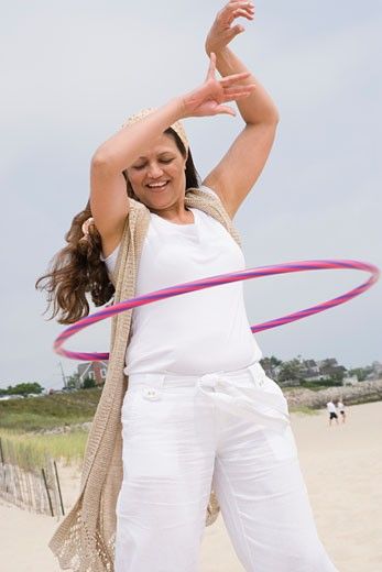 Mature woman playing with a plastic hoop on the beach : Stock Photo