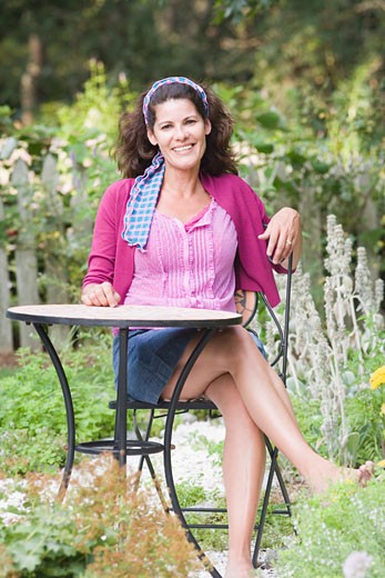 Portrait of a mature woman sitting at a table and smiling : Stock Photo