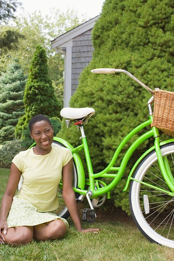 Mid adult woman sitting beside a bicycle and smiling : Stock Photo