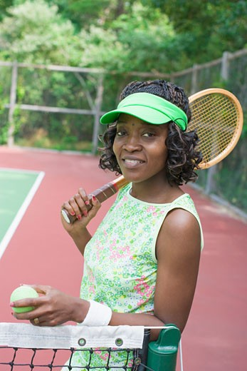 Portrait of a mid adult woman holding a tennis racket and a tennis ball : Stock Photo