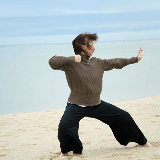 Mature woman practicing martial arts on the beach : Stock Photo