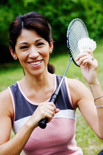 Portrait of a mature woman holding a badminton racket and a shuttlecock : Stock Photo