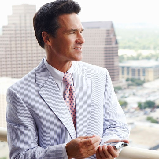 Close-up of a businessman using a personal data assistant : Stock Photo