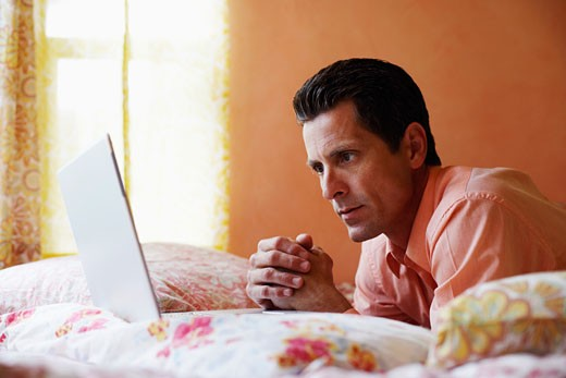 Side profile of a mature man lying on the bed and looking at a laptop : Stock Photo