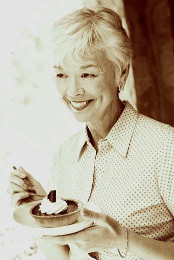 Stock Photo: 1741R-2287 Close-up of a senior woman eating a tart with a fork