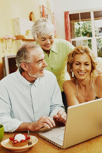 Mature couple and a senior woman smiling in front of a laptop : Stock Photo