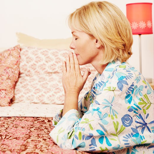 Side profile of a mature woman praying in a bedroom : Stock Photo