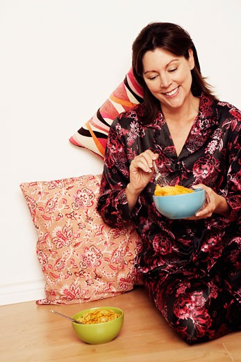 Mature woman sitting on the floor and holding a bowl of papaya : Stock Photo