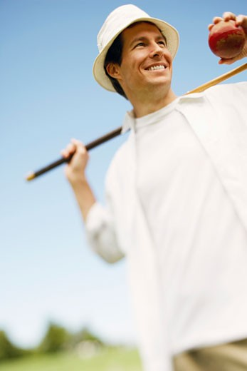 Low angle view of a mid adult man holding a croquet mallet and a ball : Stock Photo