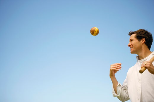 Stock Photo: 1741R-3195 Low angle view of a mid adult man tossing a ball