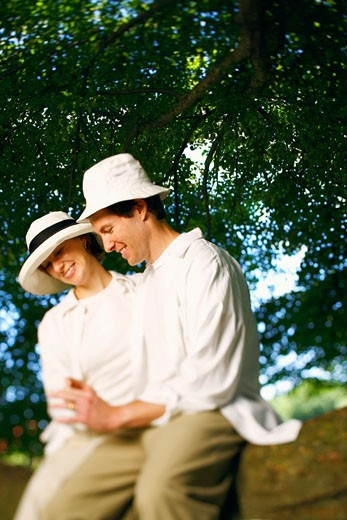 Mid adult couple sitting on a tree branch and smiling : Stock Photo