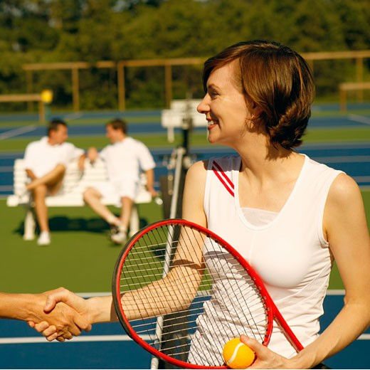 Mid adult woman shaking hands with a woman on a tennis court : Stock Photo