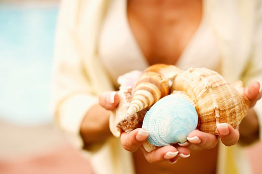 Stock Photo: 1741R-3552 Mid section view of a woman holding conch shells