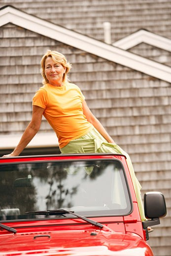 Portrait of a mature woman sitting on the top of a sports utility vehicle : Stock Photo