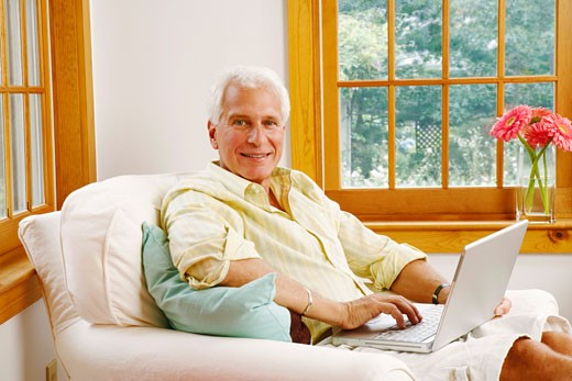 Stock Photo: 1741R-4292 Portrait of a mature man using a laptop and smiling