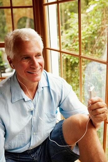 Mature man wearing headphones and listening to music : Stock Photo