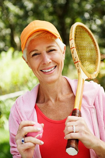 Portrait of a mature woman holding a tennis racket and a tennis ball : Stock Photo