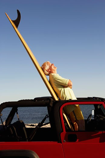 Side profile of a mature man leaning against a surfboard in a sports utility vehicle : Stock Photo