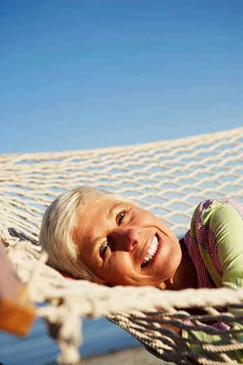 Stock Photo: 1741R-4630 Portrait of a mature woman lying in a hammock and smiling