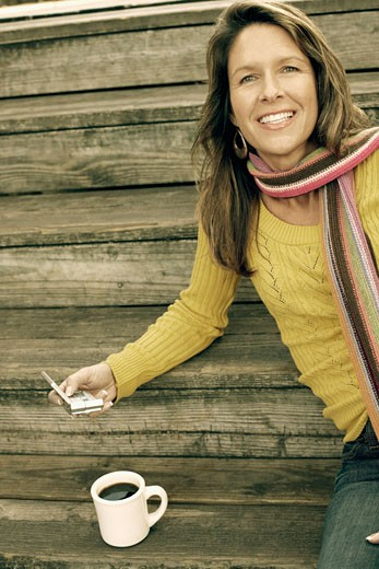 Portrait of a young woman sitting on the wooden steps with a coffee cup and holding a personal data assistant : Stock Photo
