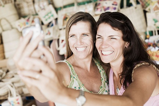 Close-up of two mid adult women holding a mobile phone and smiling : Stock Photo