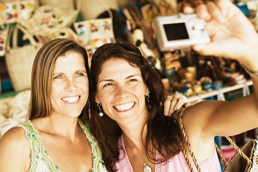 Stock Photo: 1741R-5964 Close-up of two mid adult women taking a photograph of themselves
