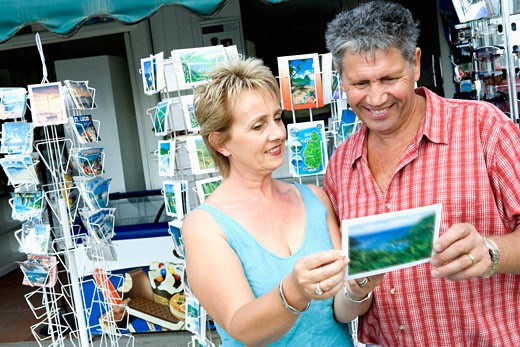 Close-up of a mature woman with a senior man holding a postcard and smiling : Stock Photo