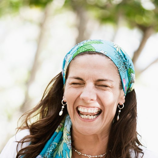 Close-up of a mid adult woman wearing a headscarf and laughing : Stock Photo