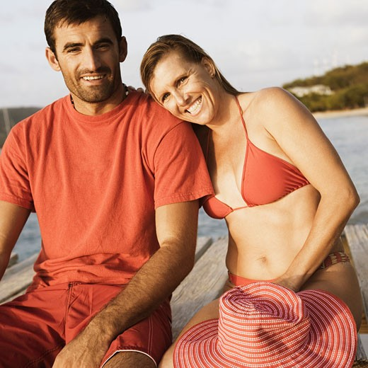 Stock Photo: 1741R-6413 Portrait of a mid adult couple sitting on a pier and smiling