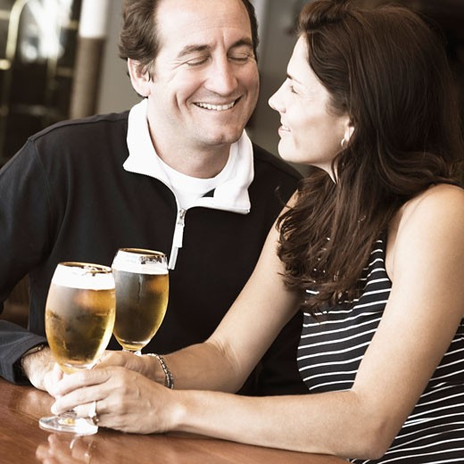 Mid adult couple sitting in a bar and holding beer in stem glasses : Stock Photo