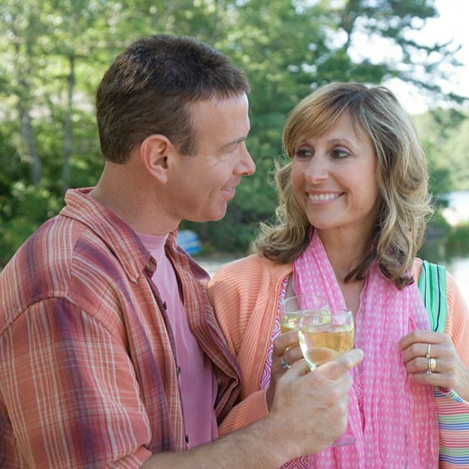 Mature couple holding glasses of wine and smiling : Stock Photo
