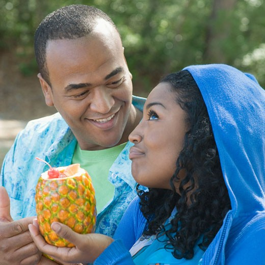 Close-up of a young woman holding a pineapple beside a mid adult man : Stock Photo