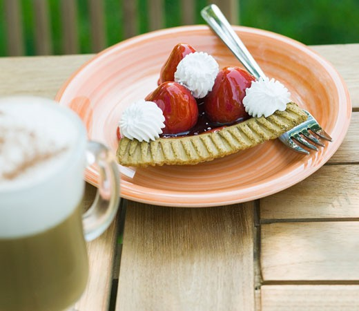 Stock Photo: 1741R-7831 Close-up of a strawberry tart and a glass of chocolate milkshake on a table