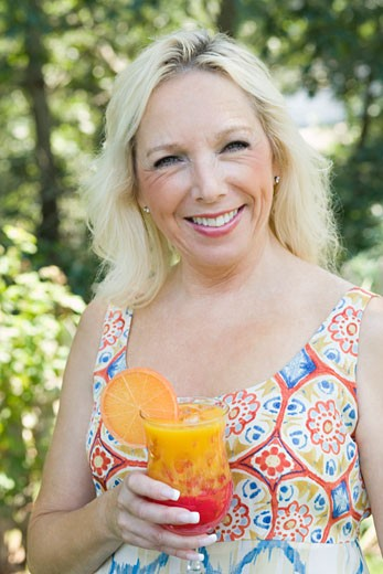 Portrait of a mature woman holding a glass of juice : Stock Photo