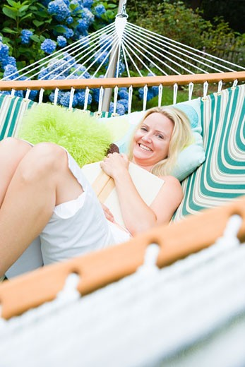 Stock Photo: 1741R-8225 Portrait of a mid adult woman lying in a hammock and smiling