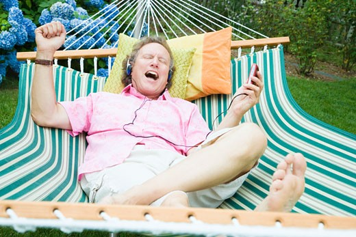 High angle view of a mature man listening to music and lying in a hammock : Stock Photo