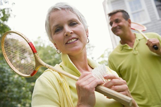 Close-up of a mature woman holding a badminton racket and a shuttlecock : Stock Photo