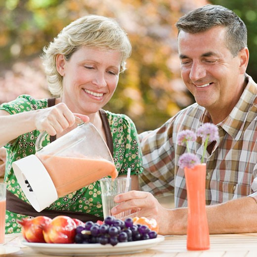 Mature couple sitting at a breakfast table and smiling : Stock Photo