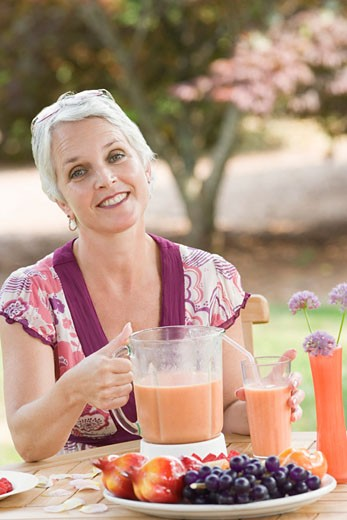 Stock Photo: 1741R-9008 Portrait of a mature woman sitting in a lawn and holding a blender filled with juice
