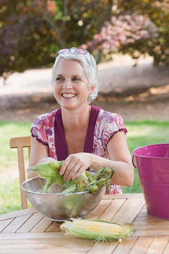 Mature woman sitting at a table and smiling : Stock Photo