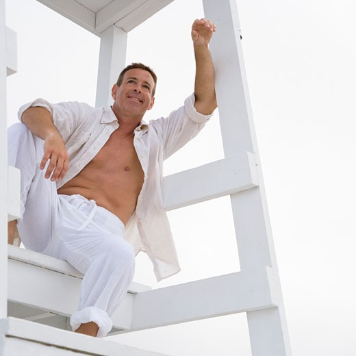 Low angle view of a mature man sitting on a lifeguard hut and smiling : Stock Photo
