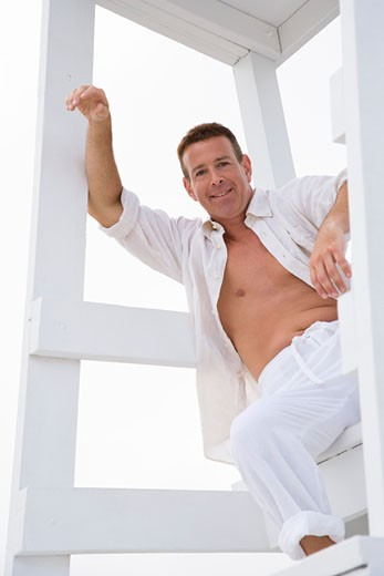 Low angle view of a mature man sitting on a lifeguard and smiling : Stock Photo