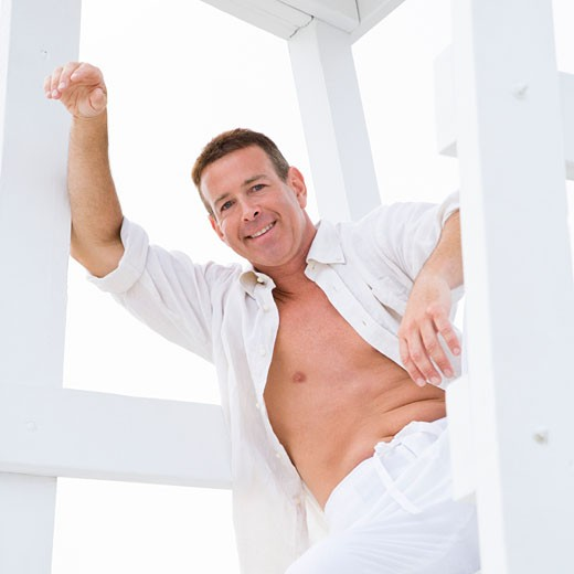 Stock Photo: 1741R-9174 Low angle view of a mature man sitting on a lifeguard hut and smiling