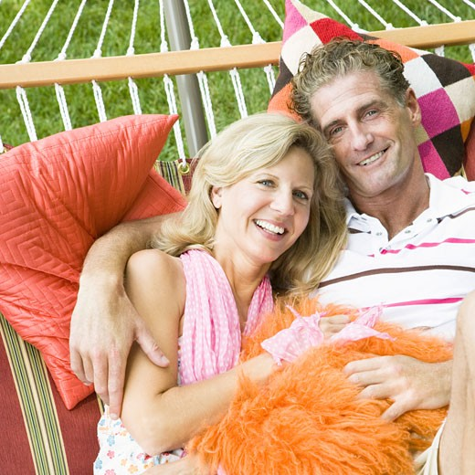 Portrait of a mature couple lying in a hammock and smiling : Stock Photo