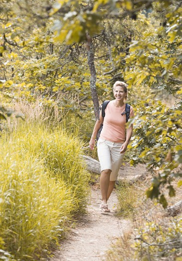 Mature woman walking in a forest and smiling : Stock Photo