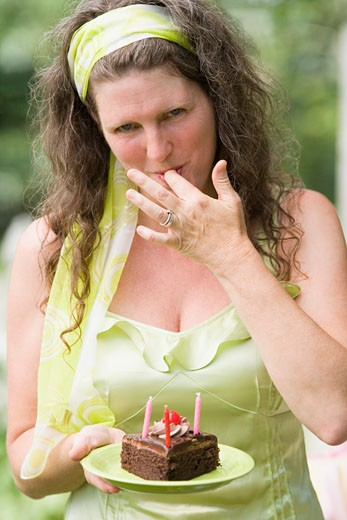 Portrait of a mature woman tasting a birthday cake slice : Stock Photo