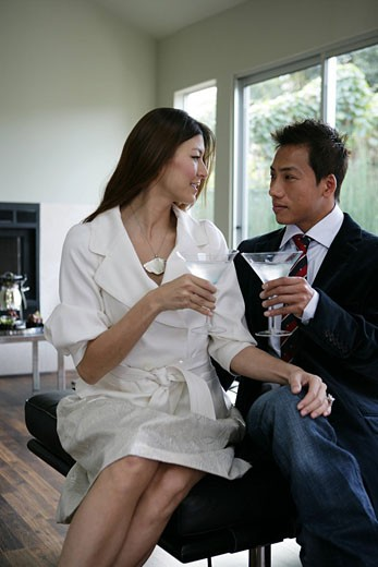 Stock Photo: 1742-11376 Young couple toasting martini glasses