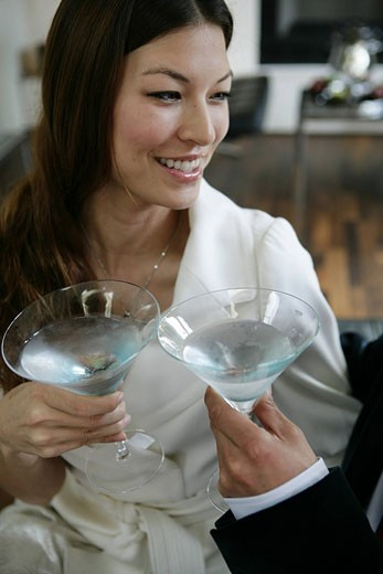 Stock Photo: 1742-11378 Woman smiling toasting martini glasses