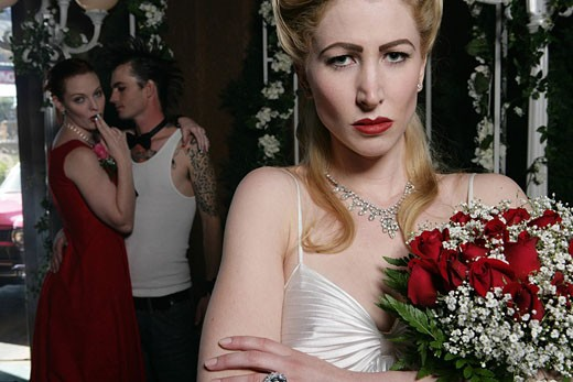 Stock Photo: 1742-11506 Unhappy woman holding a bouquet, couple in background