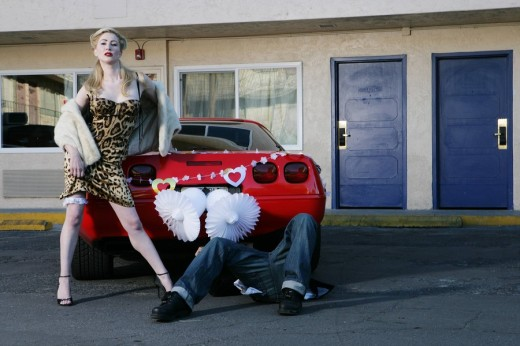 Woman flashing her garter belt, man under car : Stock Photo